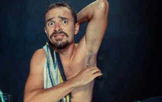 Photo of a frustrated handsome man shaving his armpit